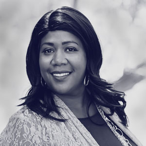 Black middle aged woman wearing a lace shawl and hoop earrings