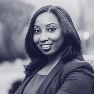 Black middle aged woman with shoulder length straight hair wearing a blazer