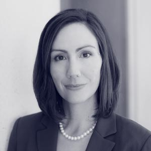 Young white woman wearing pearl neckace and suit