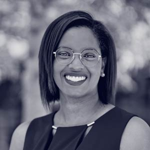 Young black woman with glasses and earrings smiling at camera