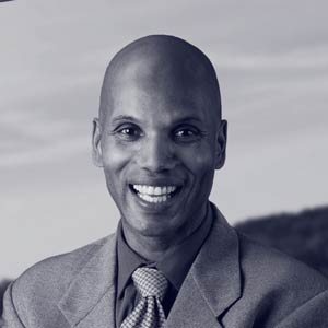 Black bald middle aged man in suit smiling at camera