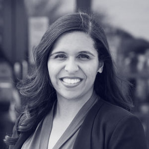 Young mexican-american woman in suit smiling at camera
