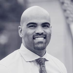 Young bald black man with goatee smiles at camera in white button up