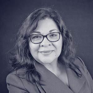 Middle aged woman with thick rimmed glasses and suit