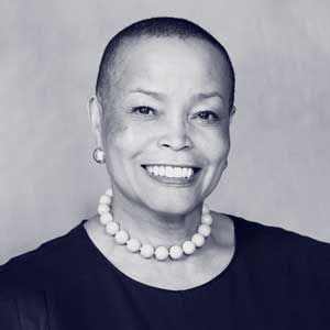 Black bald older woman wearing black shirt, pearl necklace and earrings