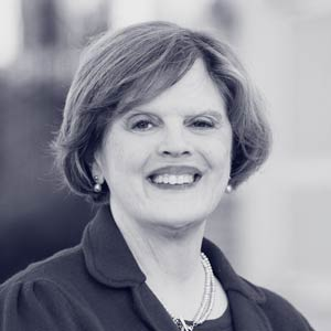 White elderly woman in dark suit smiling at camera
