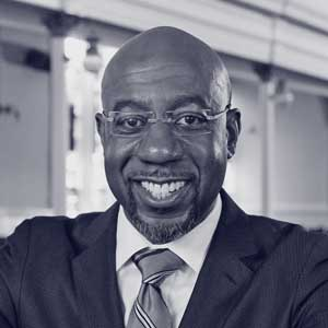 Black man with glasses and suit smiles at camera