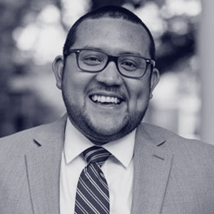 Mexican-American man with glasses and suit
