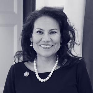 Older mexican-american woman with dark hair and pearl necklace