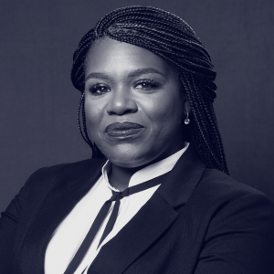 Cori Bush: Black woman with braided back hair in suit with thin ribbon tie